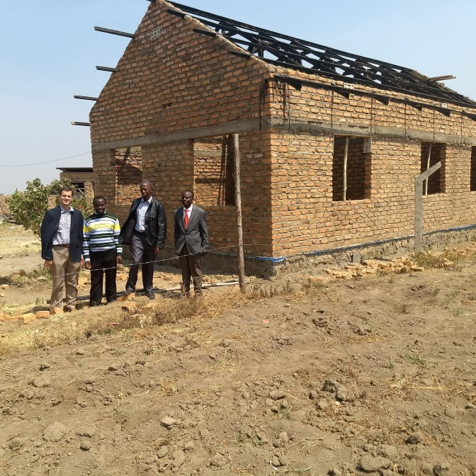 Jon stands with church leaders in front of the Biblical Learning Center under construction at our church.